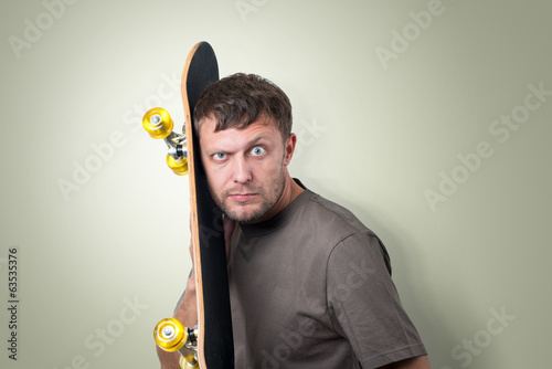 Bearded man with skateboard on green background