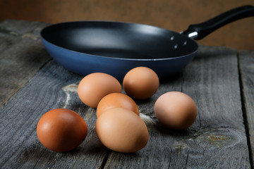 Still-life with eggs and a frying pan on boards