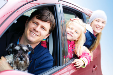 family with a dog in the car