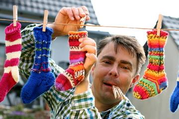 Mann mit Wäscheklammern im Mund, aufhängen