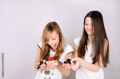 girls laughing and holding in hands nail polish