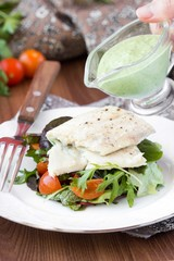 Fried white fish fillet with salad of tomatoes, arugula, herbs