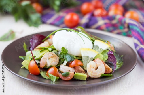 Fresh salad with shrimps, tomatoes, herbs, avocado, poached egg