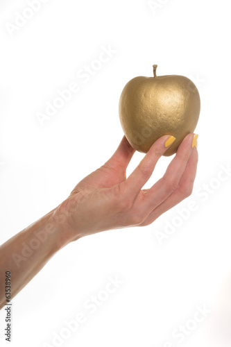 Female hand holding a gold apple