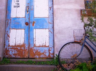 Old bicycle is parked near the door at an old house
