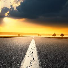 Driving on an empty asphalt road at sunrise