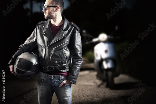 Biker on leather jacket and sunglasses holding helmet