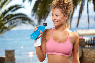 fitness and dieting concept - smiling sporty woman with bottle o