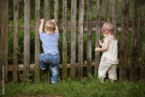 little boy and girl climbs the fence