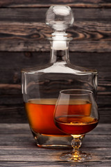 Cognac bottle and glass on wooden background