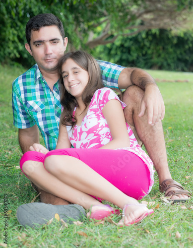 Teen girl and her father sitting in the grass at a beautiful par