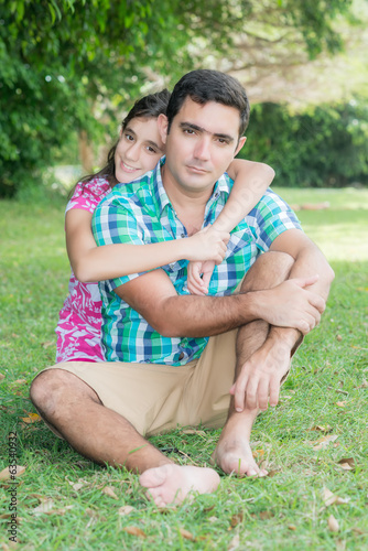 Hispanic teenage girl hugging her  father at a park outdoors