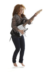 Young rock lady jumping with an electric guitar