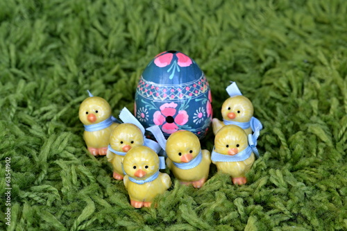 Six ceramic Easter chickens guarding painted Easter egg