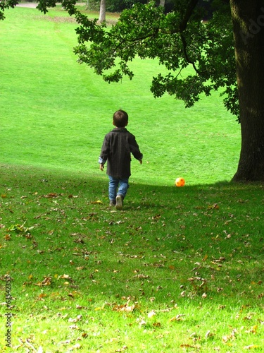 small boy walking after ball