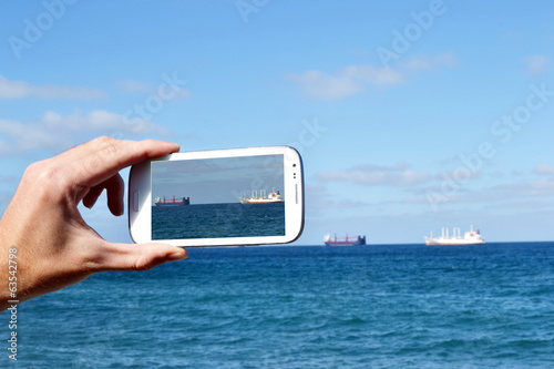 canvas print picture Taking a picture with Smartphone on beach