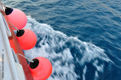 Red buoy on body of moving ship with waving adriatic sea