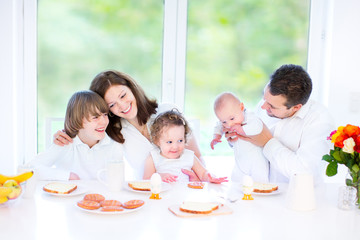 Happy young family with three children has easter breakfast