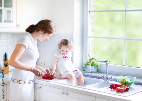 Cute toddler girl helping her mother to cook vegetables