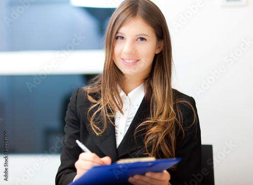 Businesswoman writing on a clipboard