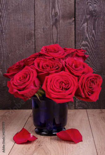 Bouquet of withered roses in blue glass vase