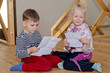 Little boy and girl sitting together reading