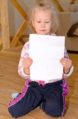 Pretty little blond girl sitting reading a letter