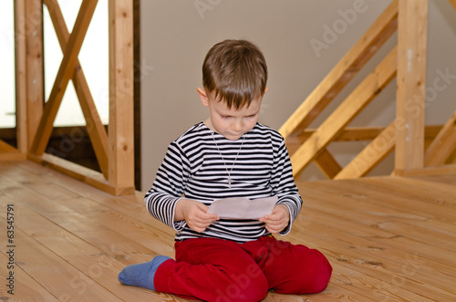 Little boy kneeling on the floor reading