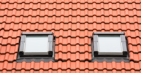 Orange roof with two classic garret windows.