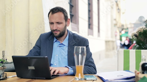 Young businessman working on modern laptop in cafe
