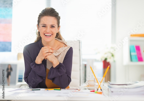 Portrait of smiling fashion designer in office