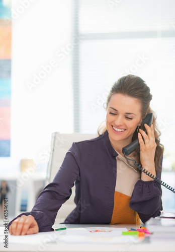 Happy fashion designer talking phone in office