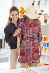 Happy fashion designer near mannequin