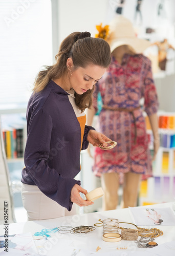 Fashion designer choosing accessories in making sketches