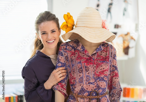 Portrait of happy fashion designer near mannequin
