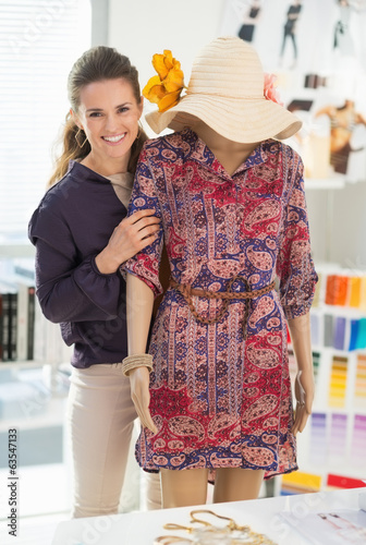 Happy fashion designer near mannequin