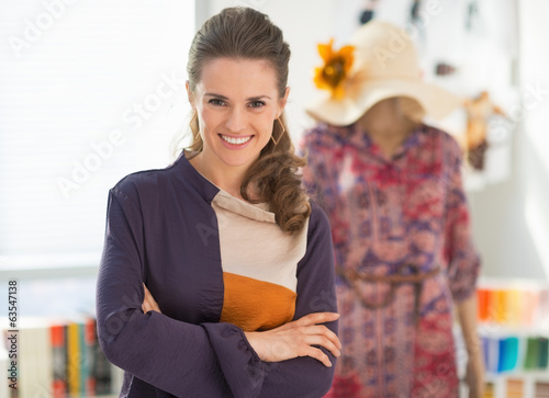 Happy fashion designer and dressed mannequin in background