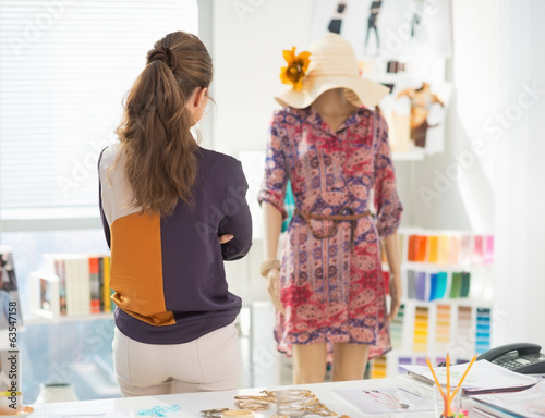 Fashion designer looking on garment
