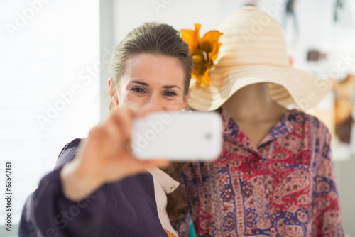 Fashion designer taking self photo with garment