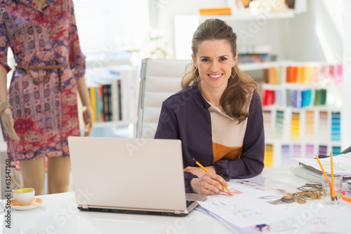 Happy fashion designer with laptop in office