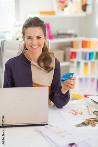 Portrait of happy fashion designer with credit card in office