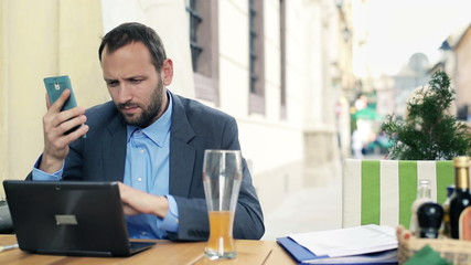 Businessman with modern laptop and smartphone sitting in cafe