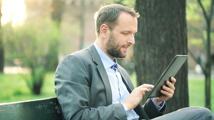 Young businessman with tablet computer sitting on bench in the p