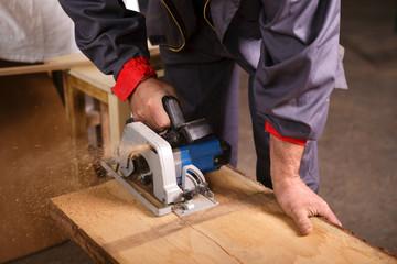 Hands carpenter working with circular saw
