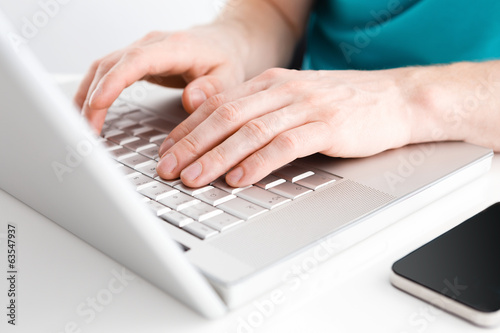 Close-up of hands typing on laptop keyboard