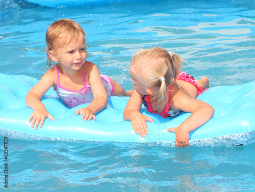 Two girls playing in a swimming pool.