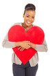 young african woman hugging red heart shape