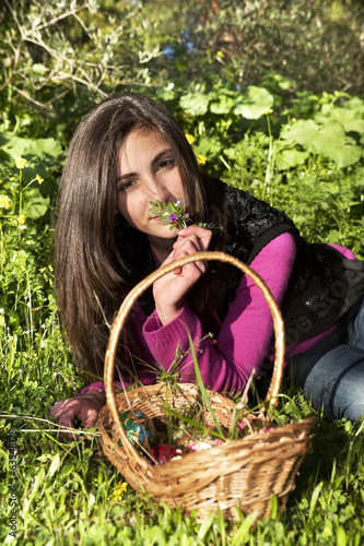 Young woman with basket of eggs picking flowers