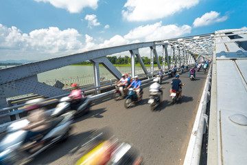 People on bikes on bridge of Hue, Vietnam, Asia.