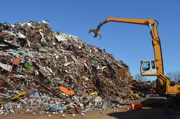 Crane grabber snatch recycling metal at a scrap-iron junk